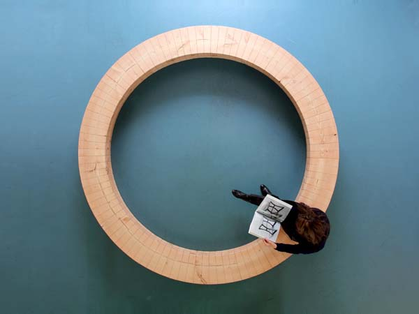 鹿特丹设计师chris kabel最近设计了环形木凳,它是由100个梯形构件组合而成的环形木座椅。这个设计的原理类似于木桶,设计师用一个金属条将所有构件组合在一起,这样既不需要粘合剂来粘贴构件,又保证了座椅的灵活性。所有100个梯形构件都是从一棵10米的大树上取材,所以设计师将主要精力放在如何在拼接时,保持木纹的一致性上。 所用的木材是俄勒冈松,这种树木原产自加拿大。这棵树被放在河里冲洗了一年,以去掉树上的木酸液。之后它又被送到荷兰,花了2年时间进行干燥。最后经过打磨上漆之后,这个直径3米的木材才成为设