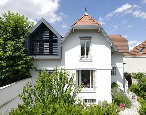 屋顶的黑色木结构与住宅的陶砖及白色背景形成对比
